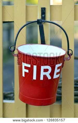 Red fire bucket hanging on picket fence