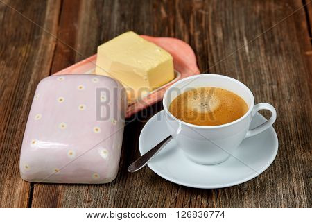 Coffee and butter on a dish on a brown wooden table
