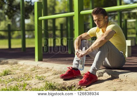 Athlete relaxing after an intense workout holding a bottle of water