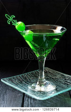 Green cocktail with maraschino cherry in a martini glasses on a glass tray and dark background