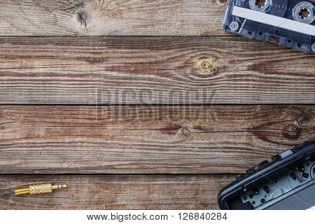 Cassette tape, cassette player and headphones over wooden table. top view.