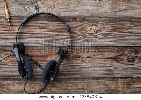 Headphones over wooden table.
