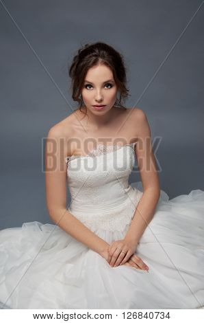 Adorable young bride with brown curly hair sitting in a cloud of tulle. Bridal fashion.