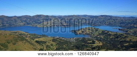 Beautiful landscape on the Banks Peninsula New Zealand. Distant view of Akaroa. Blue bay and green hills. Famous travel destination. Popular harbour for cruise ships.