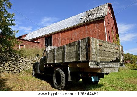 A deteriorating huge red barn has an old black truck with a wood box parked in front.