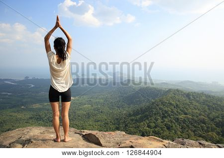 young woman practice yoga at mountain peak cliff ** Note: Soft Focus at 100%, best at smaller sizes