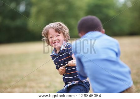 Two boys at a tug of war at the park