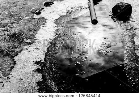 Rain puddle black and water abstract reflection with natural sunlight reflection