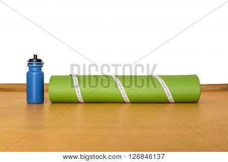 Centimeter tape yoga mat and bottle of water at gym