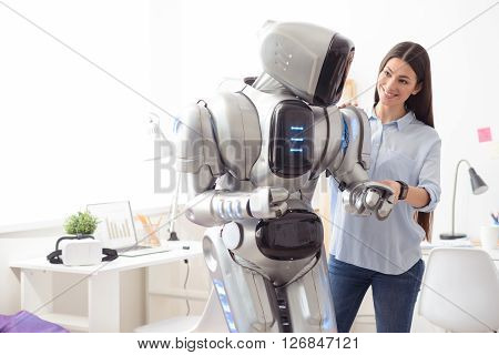 I will be with you  Delighted smiling attractive girl expressing joy and holding hand of the robot while standing in the office
