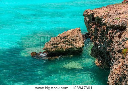 Great natural view of tropical background with crystal clear azure tranquil ocean and rocky cliff