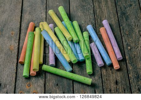 chalks in a variety of colors arranged on a wooden background