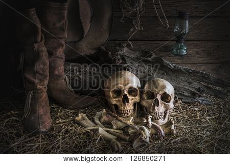 still life with human skull on hay and animal bones in traditional leather boots and american west rodeo brown felt cowboy hat background vintage and dark tone for horror halloween