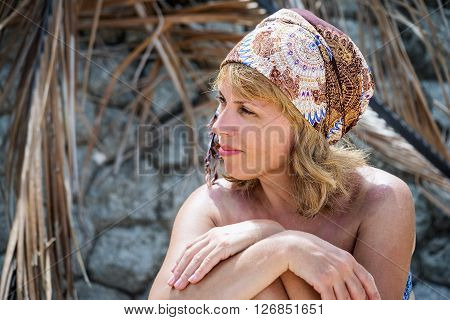 Middle Aged Beautiful Female Near Palm Leaves Near The Stone Wall And Palm Leaves In The Beach