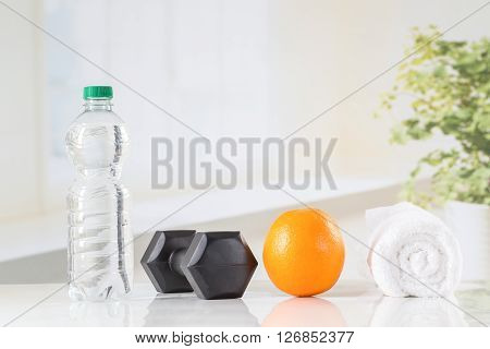 Fitness concept with water, accessories of musculation and fruit