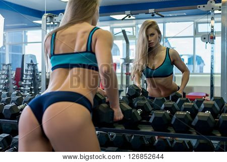 Back view of sexy girl near rack with dumbbells in gym