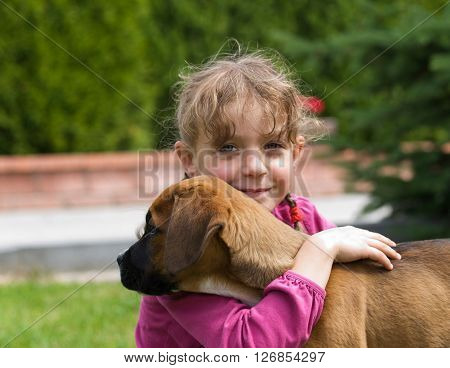 Young girl hugging her new puppy of crossbreed dog