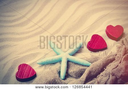 blue starfish red wooden hearts and fishnet lying on the sand