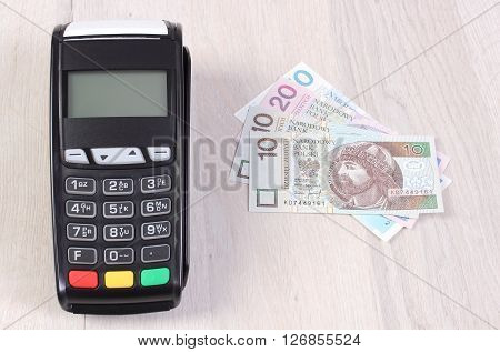 Credit card reader payment terminal with polish currency money choice between cashless or cash paying for shopping or products finance concept