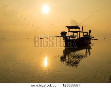 Silhouette of long tail fishing boat reflect with water sea at beach sunrise in Thailand.