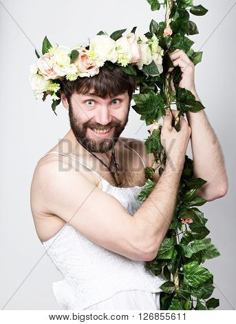 bearded man in a woman's wedding dress on her naked body, clinging to the vine. on his head a wreath of flowers. funny bearded bride.