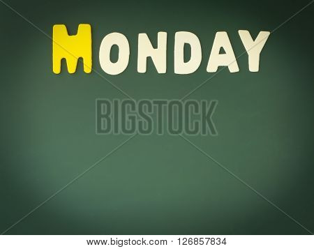 Wooden Monday on Green Board. Wood Monday word on blackboard with copy space.