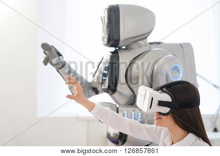Touch the world.    Pleasant  beautiful content woman holding hand in front of her  and using virtual reality device while robot standing nearby ** Note: Visible grain at 100%, best at smaller sizes