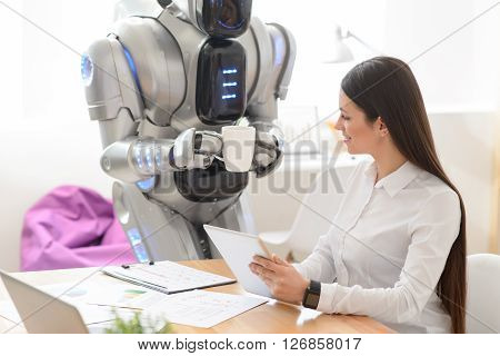 Relax a bit. Cheerful nice positive girl sitting at the table and using tablet while robot bringing a cup of coffee to her