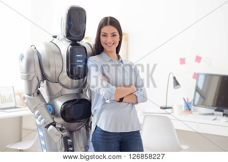 We are one team. Cheerful smiling delighted woman folding her hands and smiling while standing in the office