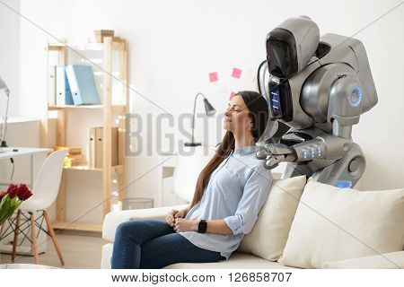 Involved in relaxation. Delighted charming pleasant girl sitting on the couch and resting while modern robot making a massage