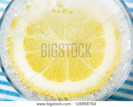 lemon with carbonate soda on a blue napkin