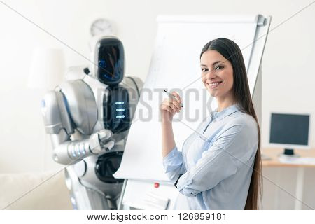 Express confidence. Cheerful attractive smiling woman holding  highlighter and folding her hand while modern robot standing in the background