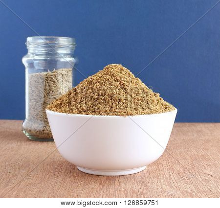 Healthy food cumin powder, home made, in a bowl and, in the background, a glass of cumin seeds.
