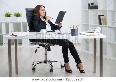 Businesswoman sitting at table in relaxed posture and making notes in book. Notebook phone tablet cup on table. Office. Concept of coffee break.