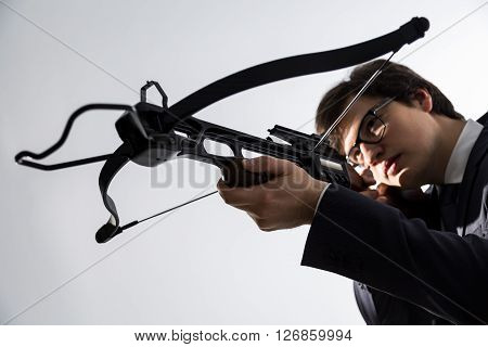 Businessman aiming with crossbow on light background