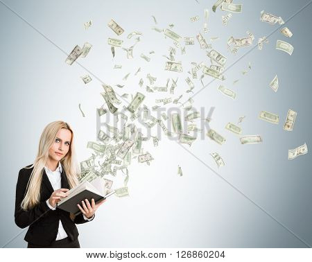 Businesswoman with money flying out of book on light grey background