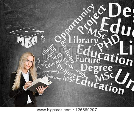 Educational concept with businesswoman and MBA cap sketch on blackboard