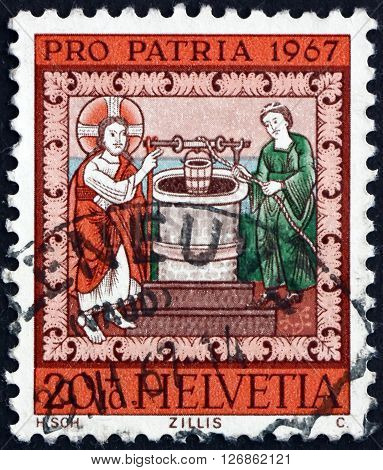 SWITZERLAND - CIRCA 1967: a stamp printed in the Switzerland shows Jesus and the Samaritan Woman at the Well circa 1967
