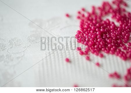 Seed Beads Of Crimson Color On The Textile Background Close Up