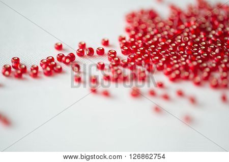 Seed Beads Of Dark Red Color On The Textile Background Close Up