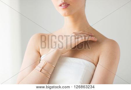 glamour, beauty, jewelry and luxury concept - close up of beautiful woman with golden ring and bracelet