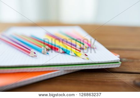 art, school, education, drawing and object concept - close up of crayons or color pencils on notebook paper