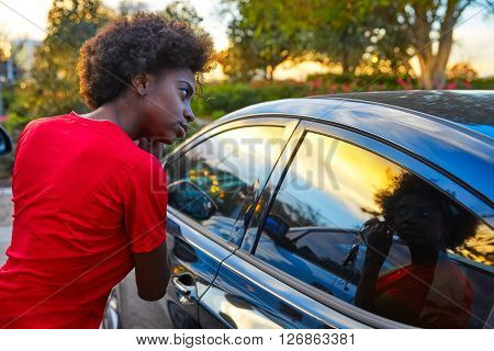 Woman fixing earings on car window glass at sunset as a mirror