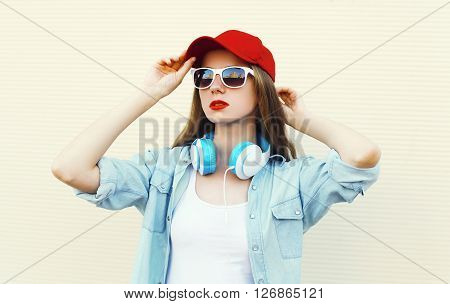 Pretty Woman In Sunglasses And Red Cap Over White Background