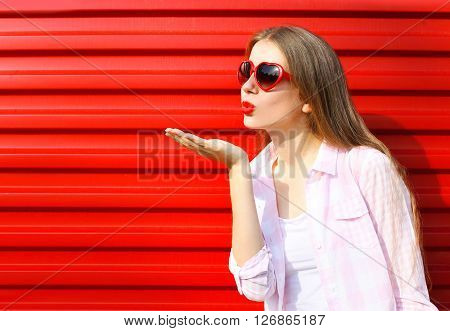Woman In Red Sunglasses Sends An Air Kiss Over Colorful Background