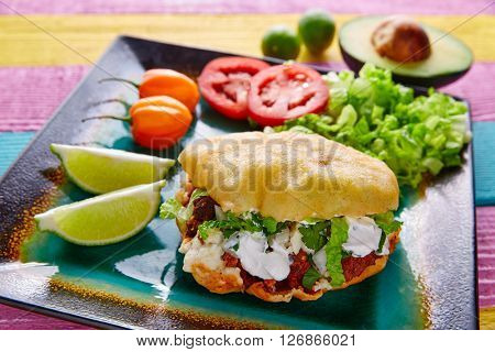 Gordita mexican fried puff corn taco filled with pastor meat lettuce and cream
