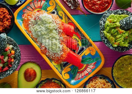 Red enchiladas Mexican food with guacamole and sauces on colorful table