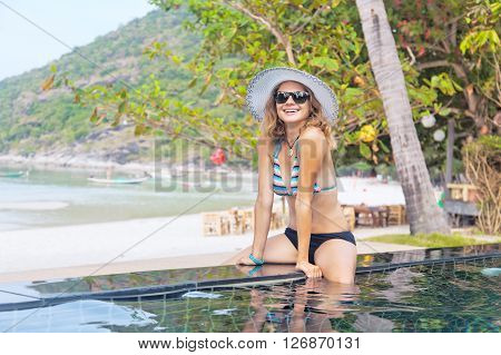Beautiful Young Woman Sitting On The Side Of The Pool On The Shore Of Tropical Sea