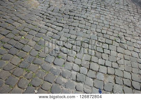 Ancient roman dilapidated small square stone paving in Rome Italy