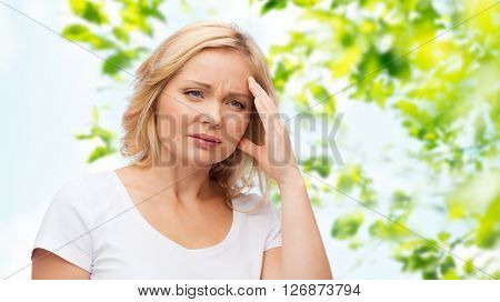 people, healthcare, stress and problem concept - unhappy woman suffering from headache over green natural background